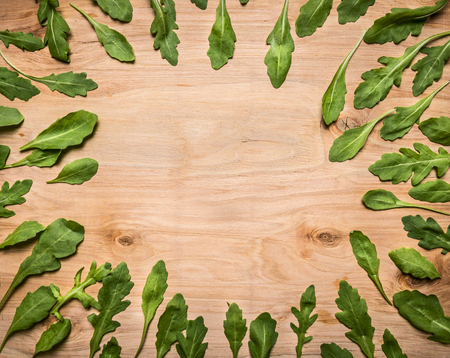 rocket lettuce: fresh arugula leaves lined frame on wooden rustic background top view place for text, on wooden rustic background top view Stock Photo