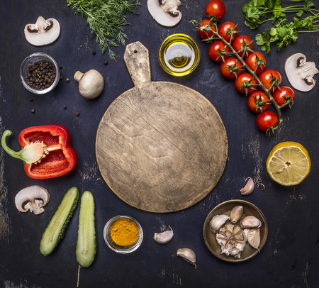 cutting board, around lie ingredients variety of vegetables and fruits, place for text,frame on wooden rustic background top view