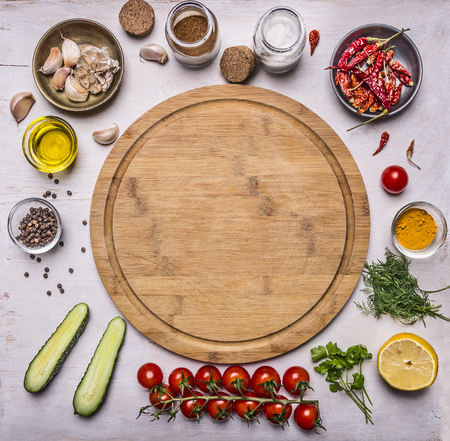 cutting board, around lie ingredients for cooking vegetarian food, tomatoes on a branch, spices, cucumbers butter place for text, frame on wooden rustic background top view Фото со стока