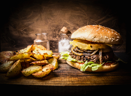 delicious homemade burger with meat, onions, lettuce and pineapple, potato wedges on wooden rustic cutting board close up Фото со стока