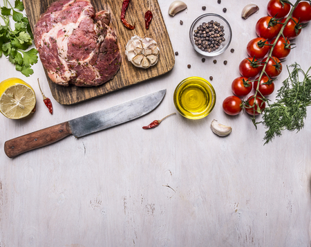 raw pork in marinade, on a cutting board with tomatoes on a branch, a knife for meat and seasonings border, place for text on wooden rustic background top view