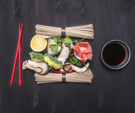 chili sauce: Ingredients for cooking Traditional Japanese buckwheat soba noodles with oyster mushrooms, cilantro, lemon and ginger, red chopsticks on wooden rustic background top view close up Stock Photo