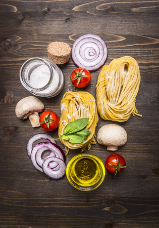 menu background: vegetarian concept cooking pasta with vegetables and mushrooms on wooden rustic background top view close up Stock Photo