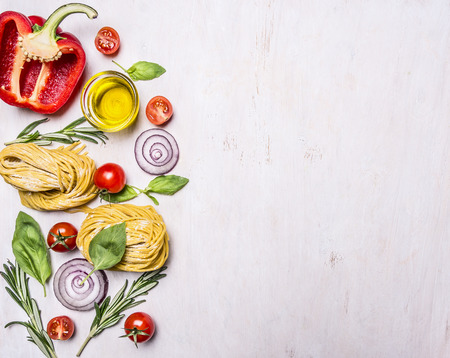 cooking and vegetarian concept raw pasta with  vegetables border with text area on wooden rustic background top view