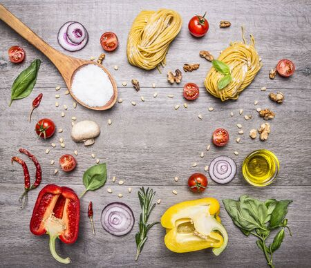 pasta: raw pasta with peppers and cherry tomatoes with a wooden spoon, salt, butter and chives on wooden rustic background top view close up place for text Stock Photo