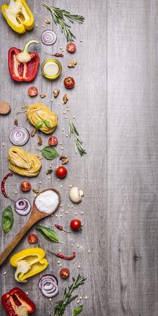 comida italiana: Ingredientes para cocinar pasta cruda con tomate, pimienta, una cuchara de madera, sal, aceite, pi�ones y hierbas en el fondo de madera r�stica vista superior frontera