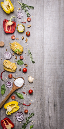 Ingredients for cooking raw pasta with tomatoes, pepper, a wooden spoon, salt, oil, pine nuts and herbs on wooden rustic background top view border Stock Photo