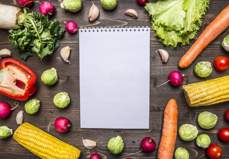 leaf vegetable: fresh vegetables and herbs laid out around a notebook for recipes on wooden rustic background top view close up border, place for text