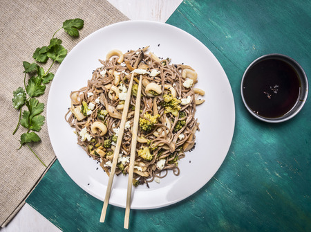pasta: Buckwheat noodles with squid and seafood on a white plate with chopsticks, soy sauce on wooden rustic background top view