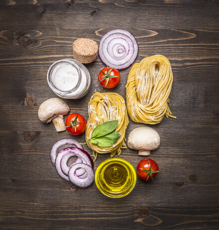healthily: pasta with fresh vegetables, preparation with flour on rustic wooden background, top view. Vegetarian food and healthily cooking concept