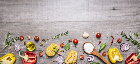 veges: Pasta, tomatoes and ingredients for cooking on rustic background, top view, border. Italian food concept Stock Photo