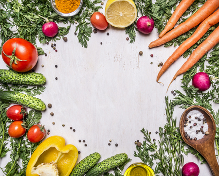 Healthy foods, cooking and vegetarian concept fresh carrots with cherry tomatoes, garlic, lemon radish, peppers, cucumbers, butter on wooden rustic background top view