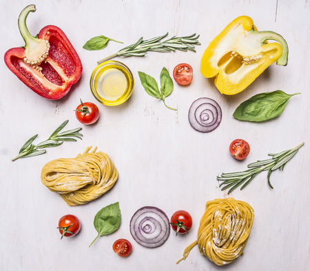 bell peppers, oil, rosemary, cherry tomatoes and other ingredients for cooking vegetarian pasta, lined frame on wooden rustic background top view border, place for text Фото со стока
