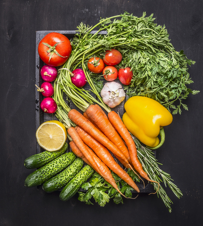 Colorful various of organic farm vegetables with fresh carrots with cherry tomatoes, garlic, lemon radish, peppers, cucumbers on wooden rustic background top view