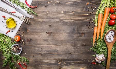 Färska ekologiska grönsaker och skedar på rustikt trä bakgrund, ovanifrån, gränsen. Hälsosam mat eller vegetarisk matlagning koncept
