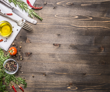 ingredients for cooking vegetarian food, tomatoes, butter, herbs, colorful peppers on wooden rustic background top view border, place for text Standard-Bild
