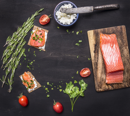 cereza: sandwiches with pink salmon fillet, curd cheese, herbs and cherry tomatoes lined frame on a black wooden background backdrop place for text, frame Foto de archivo