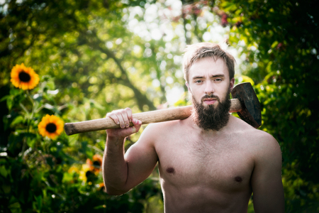 barechested: man with a beard, bare-chested, standing with a hammer on a shoulder on a natural background with sunflowers and trees