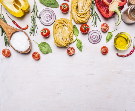 Ingredients for cooking vegetarian pasta with tomatoes, basil, oil, pepper on wooden rustic background top view border Фото со стока