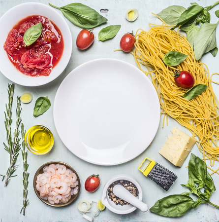 Ingredients for cooking pasta, tomatoes in own juice, basil, shrimp, grater, cherry tomatoes, laid out around a white plate place for text,frame on wooden rustic background top view