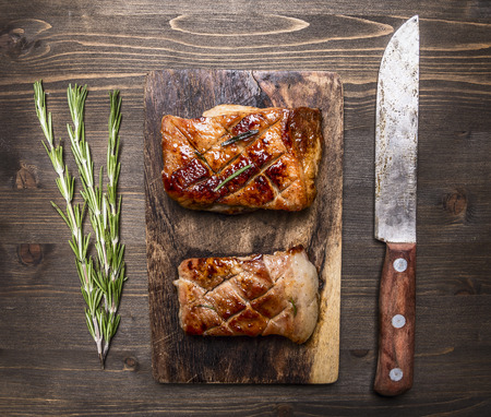 Two delicious grilled piece of pork on a cutting board with a knife for meat and rosemary on wooden rustic background top view close up