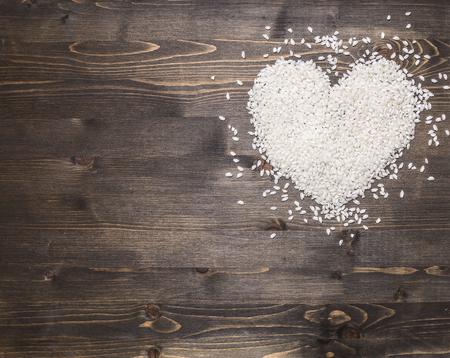 fond de texte: Coeur, étalé du riz sur un fond de bois rustique, vue de dessus, jour de valentines pour le texte, le cadre