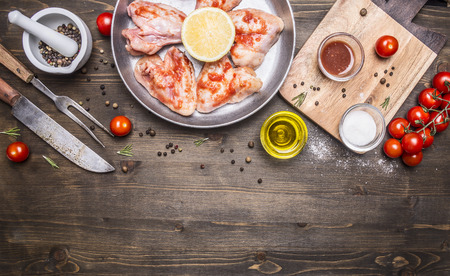 legs spread: raw chicken wings with barbecue sauce with peppers, herbs, a knife and fork, butter, herbs, cherry tomatoes on wooden rustic background top view close up border, place for text