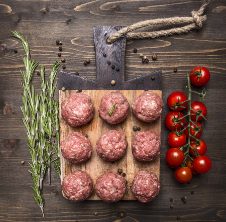 cooked pepper ball: raw meat balls with vegetables, butter and herbs on wooden rustic background top view close up