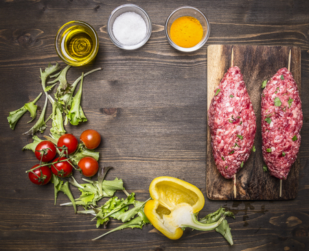 kebab: Crude kebab skewers on a chopping board with vegetables and spices on wooden rustic background top view close up place for text,frame Stock Photo