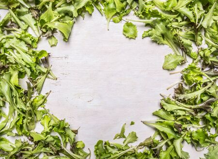 laid: Lollo rosso lettuce fresh laid out frame on wooden rustic background top view close up place for text,frame