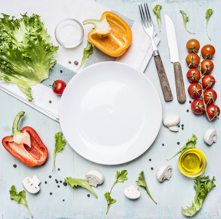 Ingredients for cooking salad cherry tomatoes, lettuce, peppers, spices and oil  laid out around a white plate on wooden rustic background top view close up Stockfoto