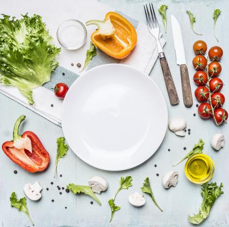 Składniki na sałatkę gotowania pomidorów cherry, sałata, papryka, przyprawy i olej rozplanowane wokół białym talerzu na drewnianym rustykalnym tle widok z góry bliska