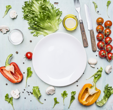 variety of vegetables laid out around a white plate with oilknife and fork on wooden rustic background top view close up Фото со стока