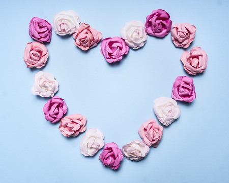 lined up: heart, lined with paper roses on a blue background  top view close up decorations for Valentines Day top view close up Stock Photo