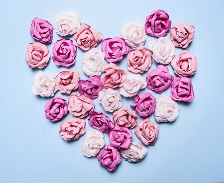 close out: colorful paper roses laid out in a heart shape on a blue background decorations for Valentines Day top view close up Stock Photo