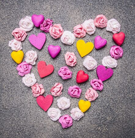 close out: colorful paper roses laid out in a heart shape on a granite background decorations for Valentines Day top view close up