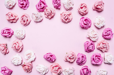 close up view: multicolored roses lined frame on a pink background top view close up place for text
