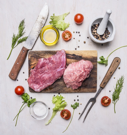 raw Pork steak with vegetables and herbs, meat knife and fork, on a cutting board on wooden rustic background top view close up