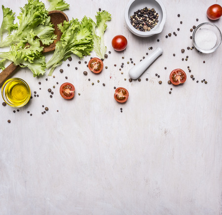 Ingredients for cooking Vegetarian Food, lettuce, cherry tomatoes, oil, salt and pepper on wooden rustic background top view close up  border ,place for text