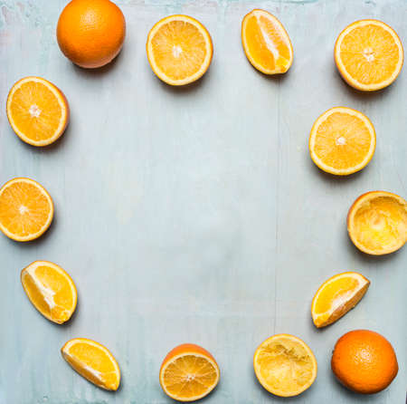 extractor: sliced oranges and juice extractor, tiled frame on blue wooden rustic background top view close up