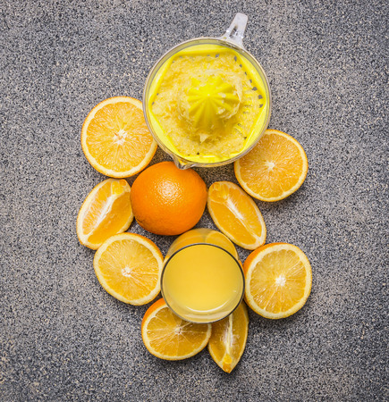 granit: sliced oranges and juicer on granit rustic background top view close up