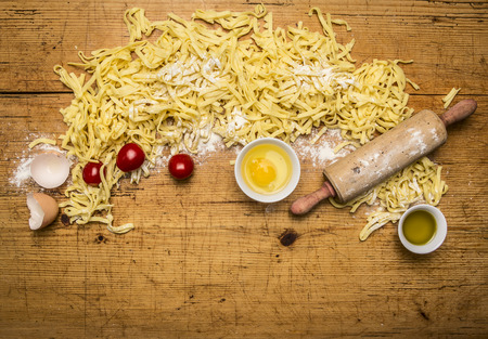 rolling up: Ingredients for cooking vegetarian pasta with tomatoes, butter, eggs, rolling pin on wooden rustic background top view close up