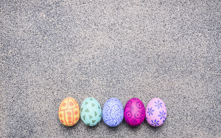 granit: bright, colorful painted eggs for Easter, laid out in a row border place for text  on granit rustic background top view close up Stock Photo