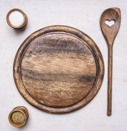 wooden board: round, vintage wooden cutting board with text area on wooden rustic background top view close up  salt and pepper and wooden spoon with heart Stock Photo