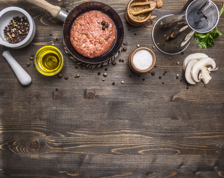 mushroom: cutlet of ground beef in a small frying pan, sliced mushrooms, pepper, herbs and salt border, place for text on wooden rustic background top view close up Stock Photo