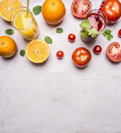 close in: fresh tomato and orange juices with mint in glasses with straws border, place for text on wooden rustic background top view close up Stock Photo