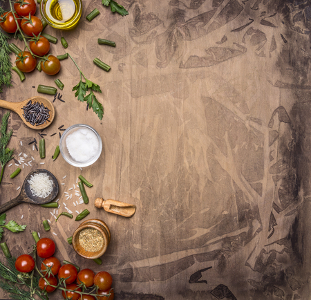 fresh concept: Ingredients for cooking vegetarian food cherry tomatoes, wild rice, spices, salt border ,place for text  on wooden rustic background top view close up Stock Photo
