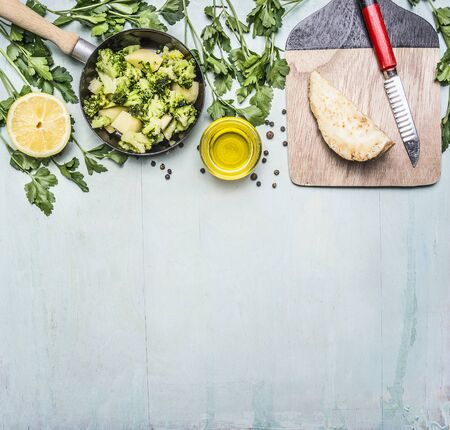 green vegetable: raw broccoli in a pan with herbs, lemon, celery root on a cutting board with a knife border, place for text on wooden rustic background top view close up
