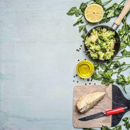 trompo de madera: brócoli crudo en una sartén con hierbas, limón, raíz de apio en una tabla de cortar con un cuchillo frontera, el lugar de texto en el fondo de madera rústica vista desde arriba de cerca