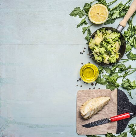 green board: raw broccoli in a pan with herbs, lemon, celery root on a cutting board with a knife border ,place for text on wooden rustic background top view close up Stock Photo